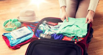 close up of woman packing travel bag for vacation PNMKHTM