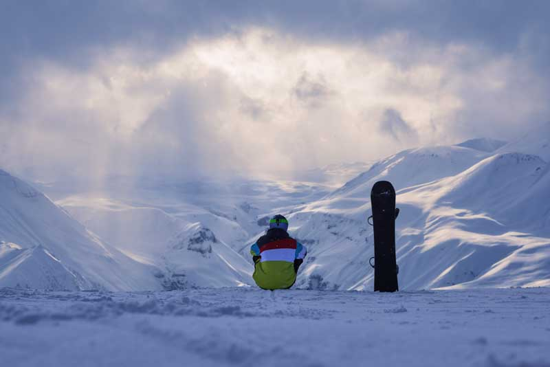 snowboarder sitting and looking at landscape of PUE2V5C