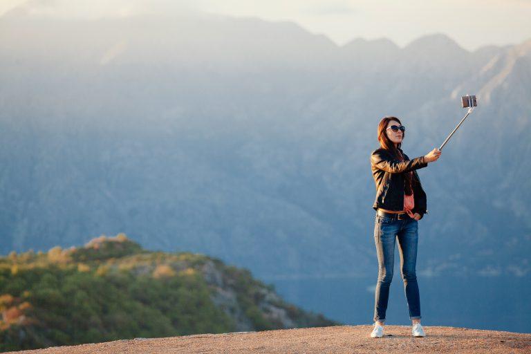 joyful woman travel and photo selfie 9XPYXUH 1