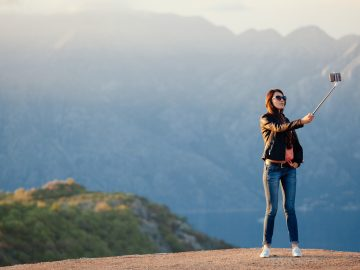 joyful woman travel and photo selfie 9XPYXUH
