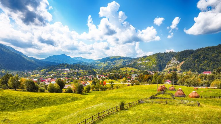 stunning alpine landscape with green fields and pi L7PNN6Y