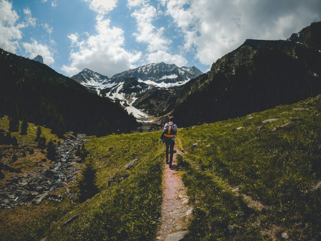 young man hiking to the mountains road trip advent ZZJTVS2